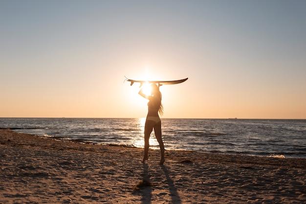 Une fille en maillot de bain tient une planche de surf au-dessus de sa tête sur la plage de sable près de la mer au coucher du soleil