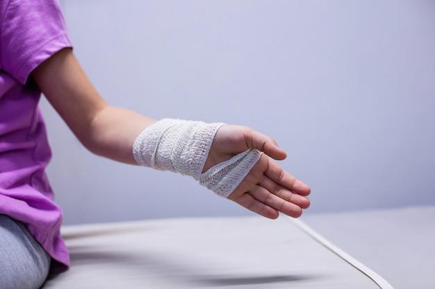 Fille avec main blessée, assis sur un lit de civière