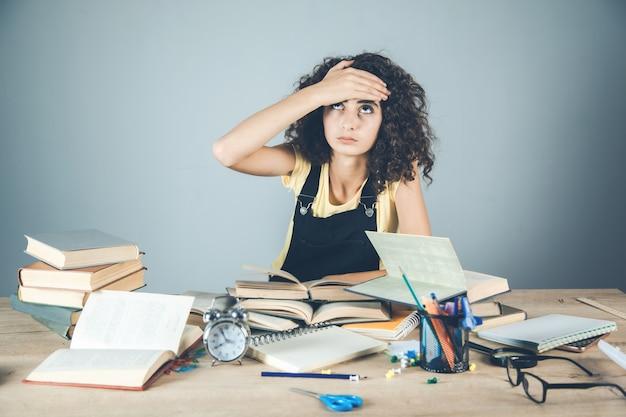 Fille main dans les cheveux avec des livres sur le bureau