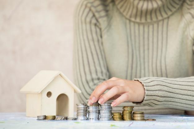 Fille main mettant l'argent pièce pile d'affaires finance et bancaire pour la maison et économiser de l'argent