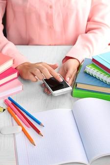 Fille de main avec smartphone sur la vue de dessus de table