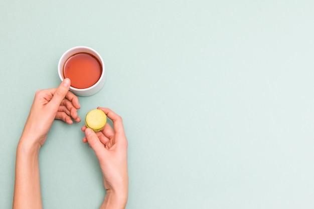 Fille mains tenant la tasse de thé et macaron, vue de dessus