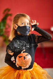 Fille à la maison en costume d'halloween avec potiron jack ou laurent dans les mains, enfant portant un masque noir protégeant du coronavirus, halloween en quarantaine