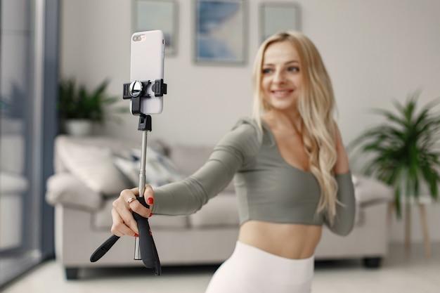 Fille à la maison. femme fait du yoga. lady tourne un blog vidéo.