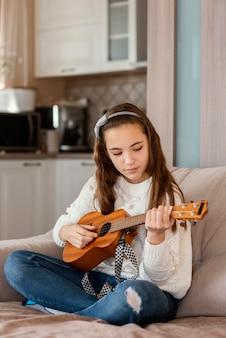 Fille à la maison à jouer de la guitare
