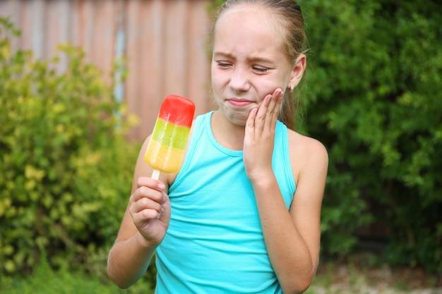Fille a mal aux dents de la crème glacée froide.