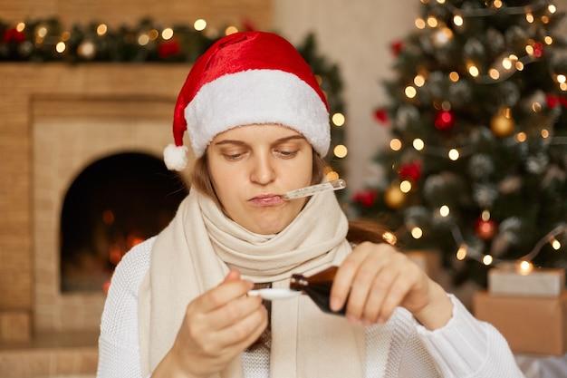 Fille malade en bonnet de noel, enveloppée dans une écharpe, versant du sirop contre la toux dans une cuillère, regardant des médicaments et mesurant la température avec un thermomètre dans la bouche, une dame posant à l'intérieur près d'une cheminée et d'un arbre de noël.