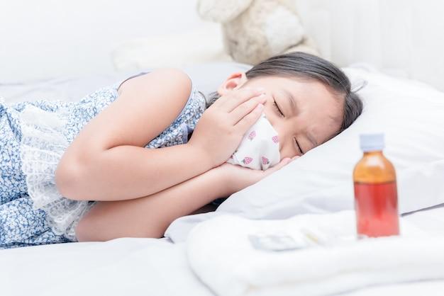 Fille malade couché dans son lit et maux de gorge et de la toux