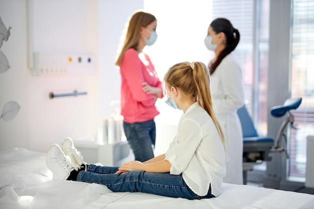 Une fille malade est assise à la recherche de la mère à parler avec le médecin à l'hôpital, en attente de solution, comment traiter, dans des masques médicaux coronavirus (covid-19. se concentrer sur la fille