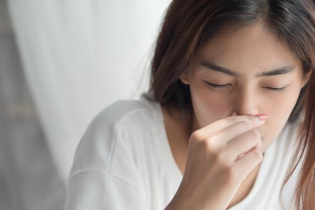 Fille malade avec nez qui coule et anosmie, perte de l'odorat en tant que symptômes d'infection covid-19
