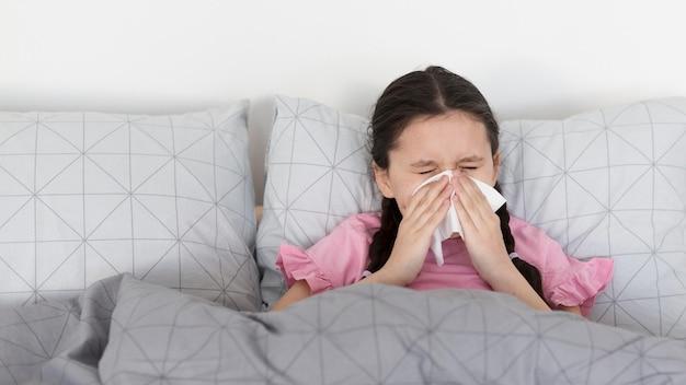Fille malade soufflant du nez