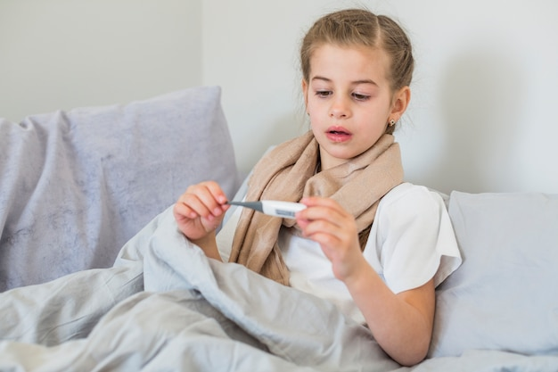 Fille malade utilisant un thermomètre