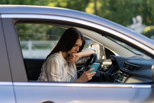 Une fille malheureuse pleure en lisant un message sms dans un smartphone au volant d'une voiture bouleversée par une femme rompant avec son petit ami