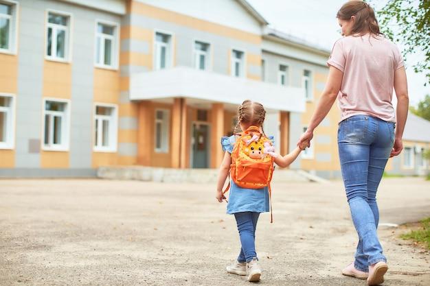 Fille avec des mallettes près de l'école.