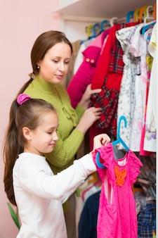 Fille et maman choisissant des vêtements
