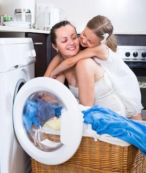 Fille et maman près de la machine à laver
