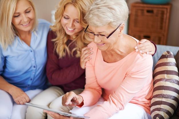 Fille avec maman soutenant grand-mère qui utilise une tablette numérique d'apprentissage