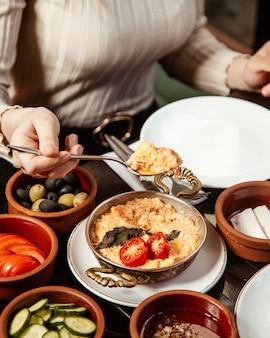 Fille mange de la bouillie avec des tomates, des légumes et des olives sur la table