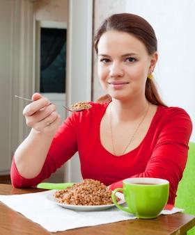 Fille mange du sarrasin avec une cuillère