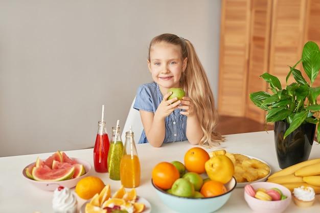 Fille mange des fruits sur une table pleine de nourriture