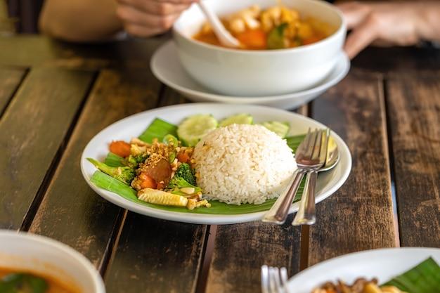 Fille mange de la nourriture thaïlandaise - soupe tom yam et riz thaïlandais avec garniture
