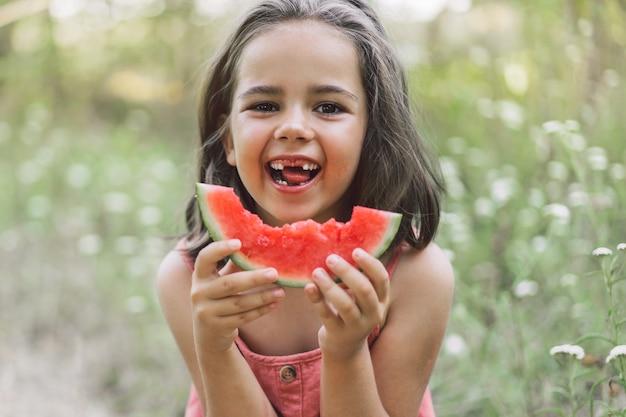 La fille mange une pastèque. ambiance estivale.