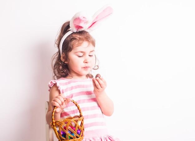 La fille mange des petits oeufs de chocolat après la chasse de pâques