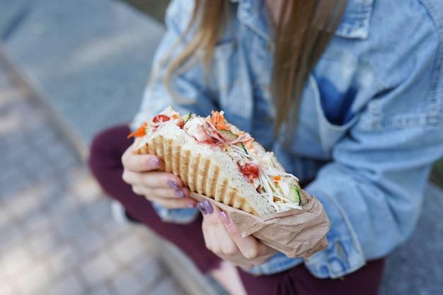 Fille mange shawarma dans la rue