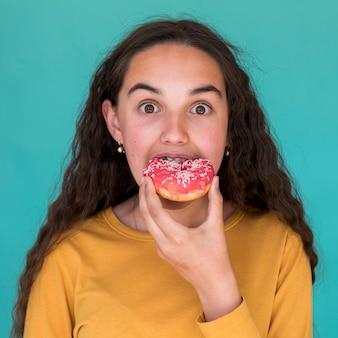 Fille mangeant un délicieux beignet