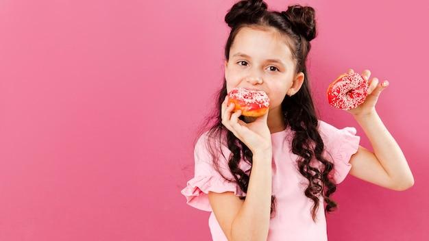 Fille mangeant de délicieux beignets avec espace de copie