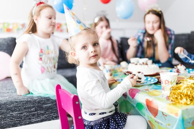 Fille mangeant un gâteau et regardant la caméra
