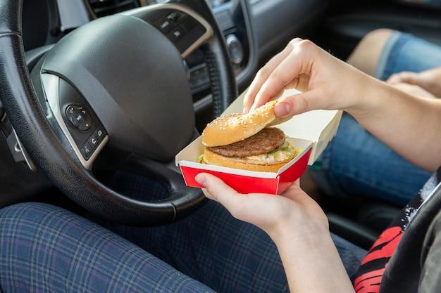 Fille mangeant un hamburger assis dans une voiture snacks à emporter de restauration rapide sur la route