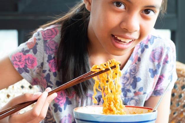 Fille mangeant des nouilles de corée instantanées, elle utilise des baguettes pour les vermicelles chinois dans la bouche