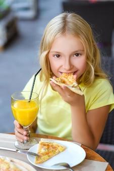 Fille mangeant de la pizza et boire du jus en plein air