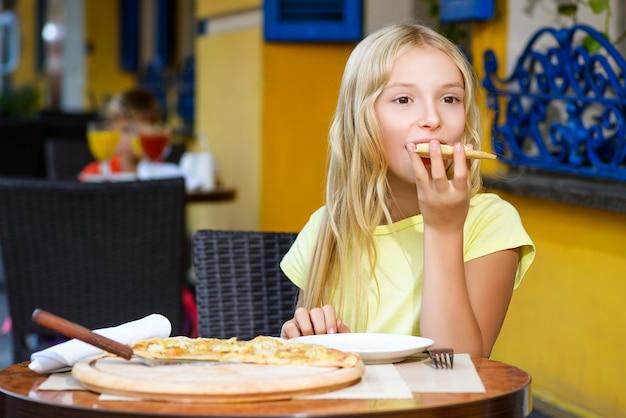 Fille mangeant une pizza à la pizzeria