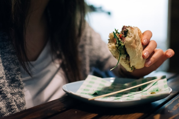 Fille mangeant un sandwich au steak argentin