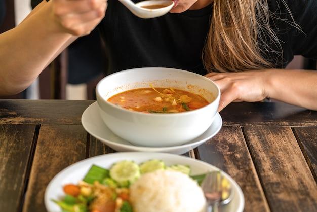 Fille mangeant tom yam kung, cuisine thaïlandaise. fermer