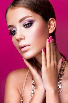 Fille de mannequin de beauté avec maquillage lumineux, cheveux longs, ongles manucurés. femme glamour isolée sur fond de studio rose.