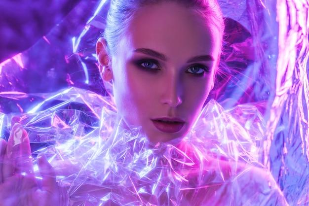 Fille de mannequin haute couture dans des néons lumineux colorés posant