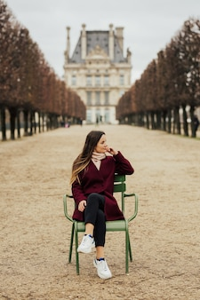 Fille en manteau bordo assis sur la chaise en face du musée du louvre à paris, france.