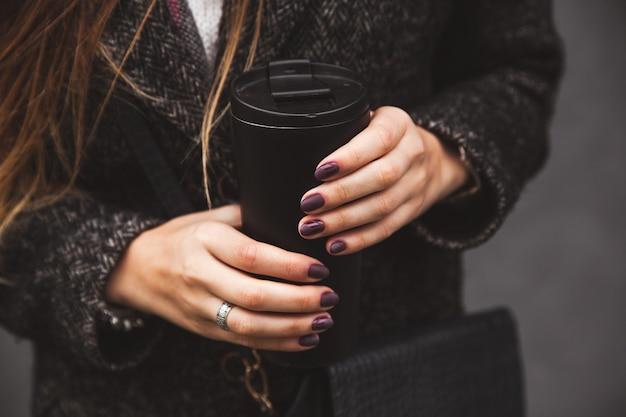 Fille en manteau élégant avec une belle main de manucure tenant un gobelet sous vide noir sur un mur gris