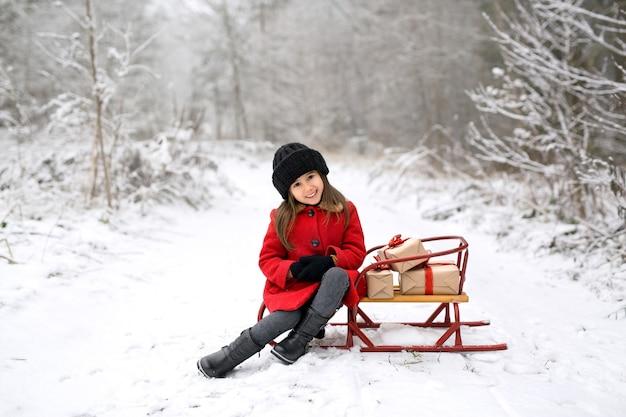 Une fille en manteau est assise sur un traîneau avec des cadeaux de noël dans un hiver enneigé