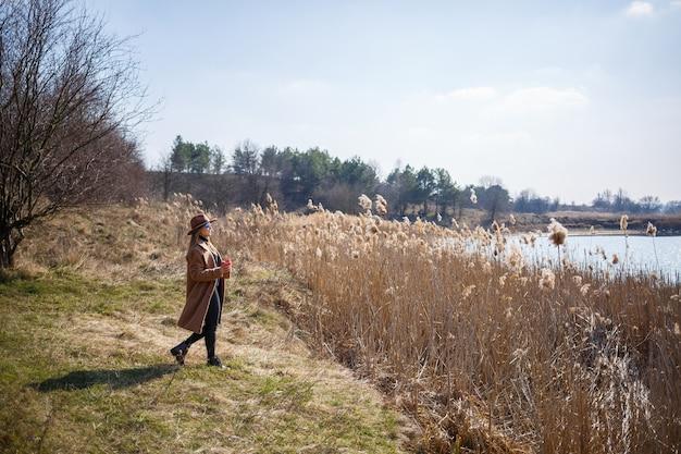 Une fille en manteau marron, chapeau et lunettes se promène dans un parc avec un lac sous le soleil éclatant. boire du thé dans une tasse en papier. le début du printemps