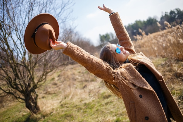 Une fille en manteau marron, chapeau et lunettes se promène dans un parc avec un lac sous le soleil éclatant. se réjouit de la vie et sourit. le début du printemps