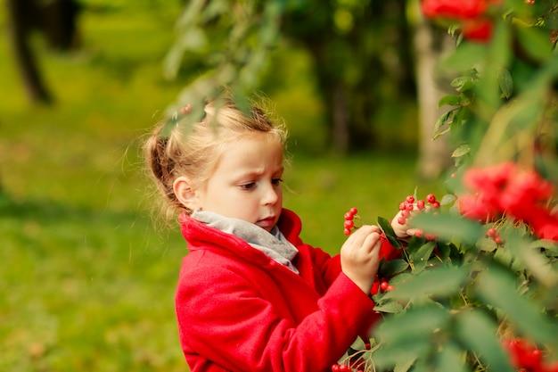 Fille en manteau rouge avec les feuilles de l'automne dans le parc.
