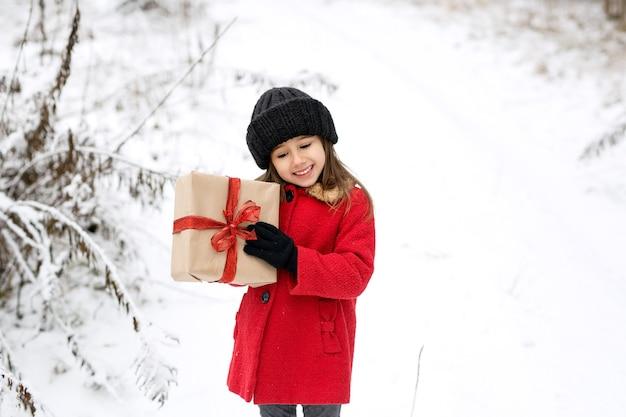 Une fille en manteau se tient au milieu d'une forêt enneigée avec un cadeau
