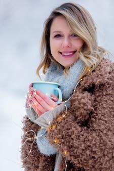 Fille en manteau avec une tasse de boisson dans une forêt de neige