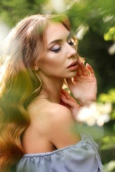 Fille avec maquillage et coiffure dans un gros plan de jardin fleuri