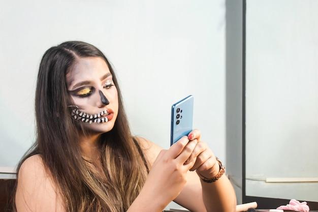 Fille avec le maquillage de crâne d'halloween à l'aide de son téléphone intelligent dans sa chambre