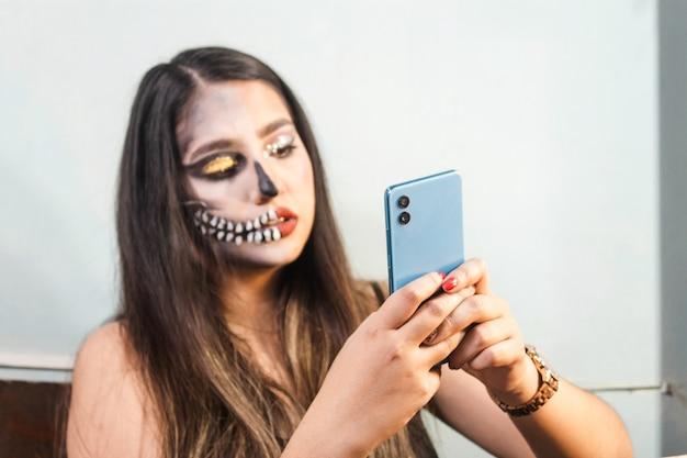 Fille avec le maquillage d'halloween à l'aide de son téléphone intelligent dans sa chambre
